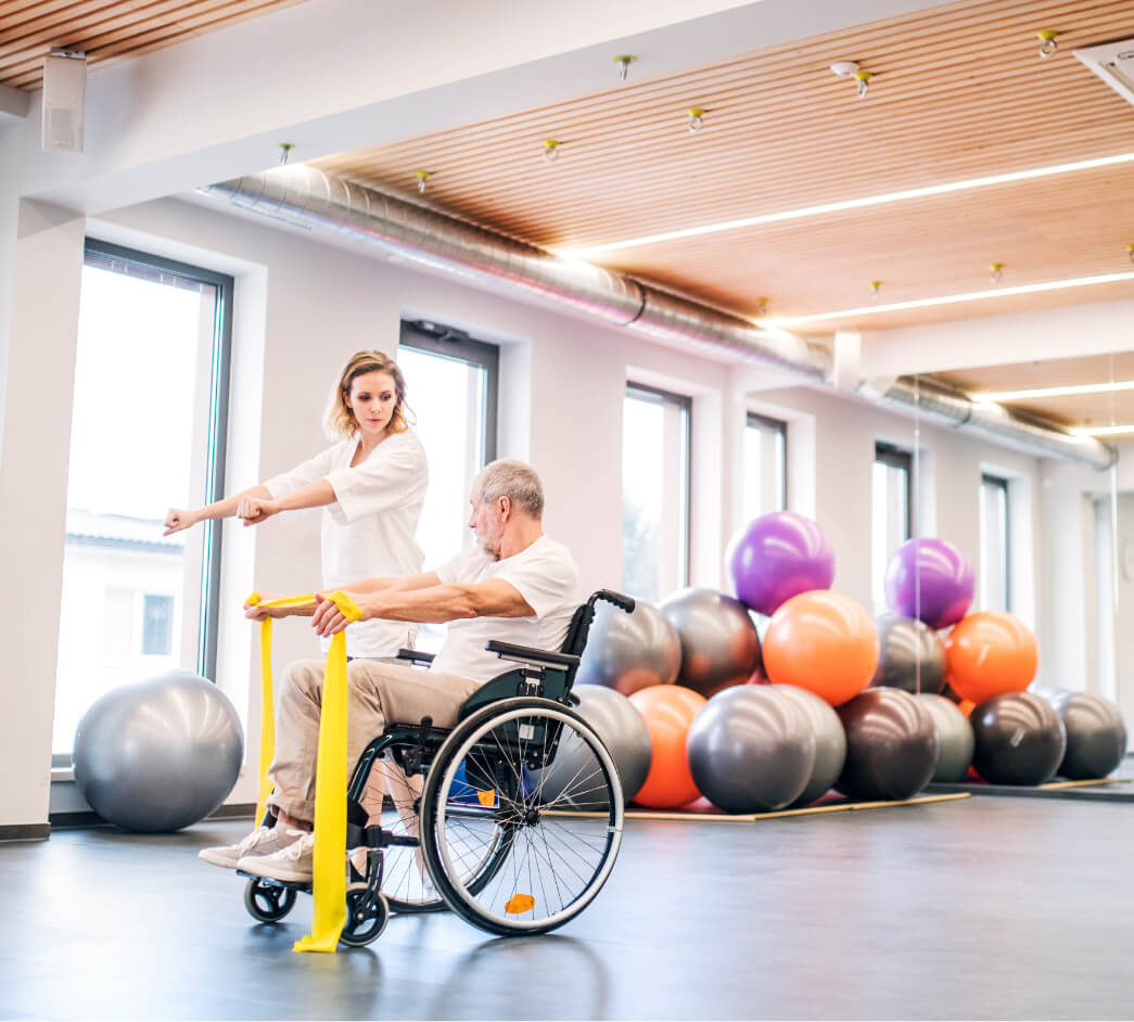 A physiotherapist showing a man in a wheelchair how to do an exercise.