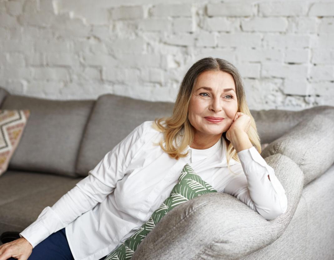A happy lady sitting on her sofa.