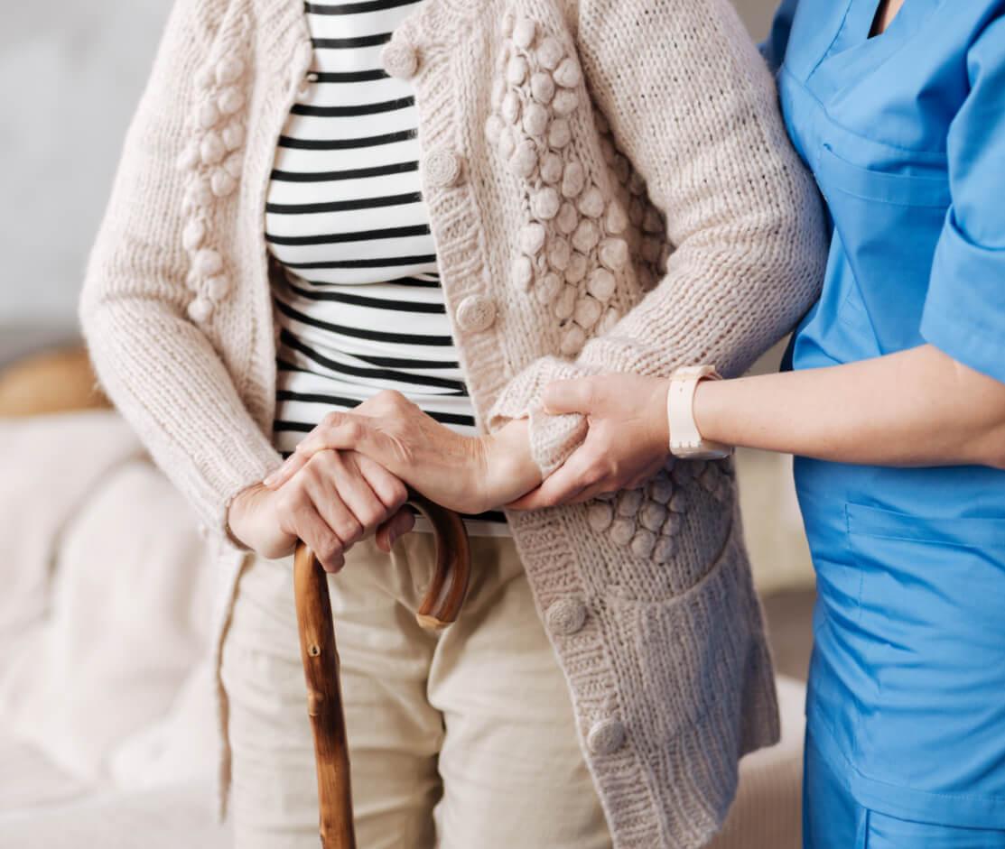 A nurse helping an older lady walk.